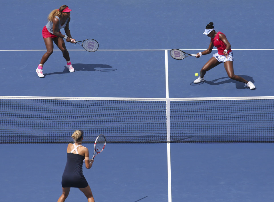 Photo - Venus Williams, right, misses a shot from Elena Vesnina, center, as Serena Williams, left, looks on during a quarterfinals doubles match against Vesnina and Ekaterina Makarova, of Russia, during the 2014 U.S. Open tennis tournament, Tuesday, Sept. 2, 2014, in New York. (AP Photo/John Minchillo)