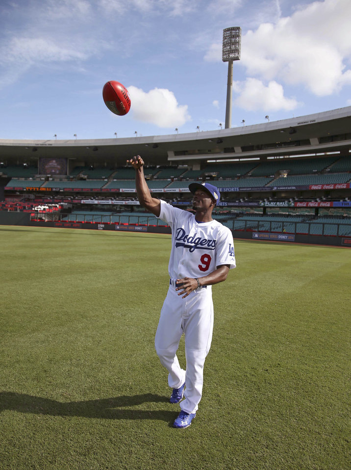 Photo - The Los Angeles Dodgers' Dee Gordon throws an Australian rules football during a training at the Sydney Cricket Ground in Sydney, Wednesday, March 19, 2014. The MLB season-opening two-game series between the Los Angeles Dodgers and Arizona Diamondbacks in Sydney will be played this weekend. (AP Photo/Rick Rycroft)