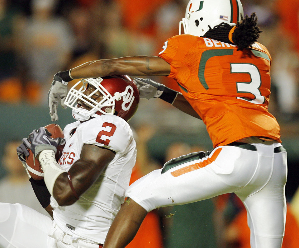 Photo - OU's Brian Jackson (2) intercepts a pass intended for Miami's Travis Benjamin (3) in the first quarter of the college football game between the University of Oklahoma (OU) Sooners and the University of Miami (UM) Hurricanes at Land Shark Stadium in Miami Gardens, Florida, Saturday, October 3, 2009. Photo by Nate Billings, The Oklahoman ORG XMIT: KOD