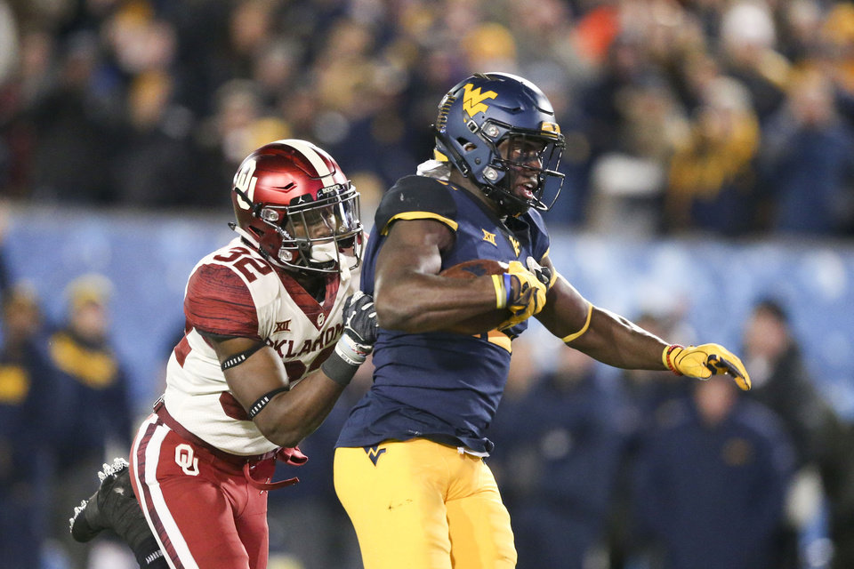 Photo - Oklahoma Sooners safety Delarrin Turner-Yell (32) tackles West Virginia Mountaineers wide receiver Gary Jennings Jr. (12) during the NCAA football game between the Oklahoma Sooners and the West Virginia Mountaineers at Mountaineer Field at Milan Puskar Stadium in Morgantown, W.Va on Friday, November 23, 2018. IAN MAULE/Tulsa World
