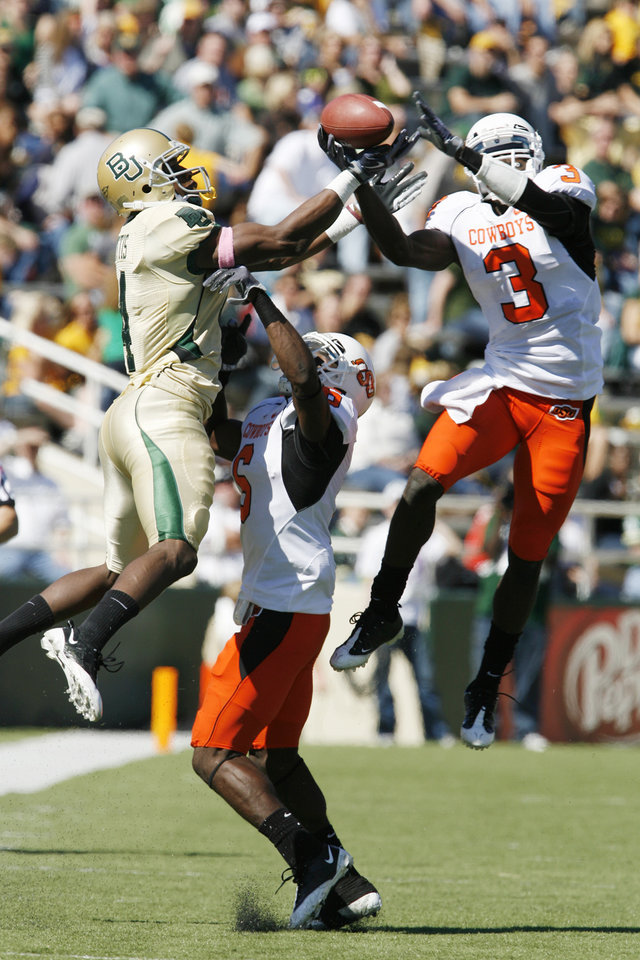 Photo - David Gettis (4 left) and Victor Johnson (3) go up for a Nick Florence pass and Getitis is called or interference during the second half of the college football game between Baylor University and Oklahoma State University (OSU) at Floyd Casey Stadium in Waco, Texas, on Saturday, Oct. 24, 2009. at bottom is Andrew McGee (6).   Photo by Steve Sisney, The Oklahoman