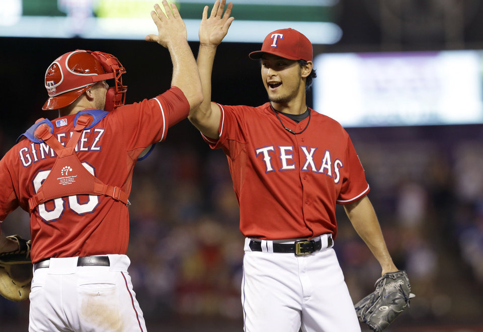 Photo - Texas Rangers starting pitcher Yu Darvish, right, of Japan, celebrates with catcher Chris Gimenez after the final out of the ninth inning of a baseball game against the Miami Marlins in Arlington, Texas, Wednesday, June 11, 2014. The Rangers won 6-0. (AP Photo/LM Otero)