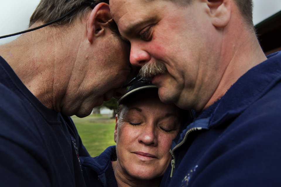 Photo - Darrington Fire District 24 volunteer firefighters, Jeff McClelland, left, Jan McClelland, center, and Eric Finzimer embrace each other Wednesday, March 26, 2014, in Darrington, Wash., after saying a prayer for the victims and survivors of the massive mudslide. They were among the first responders to the mudslide. (AP Photo/The Seattle Times, Marcus Yam)  SEATTLE OUT; USA TODAY OUT; MAGS OUT; TELEVISION OUT; NO SALES; MANDATORY CREDIT TO BOTH THE SEATTLE TIMES AND MARCUS YAM