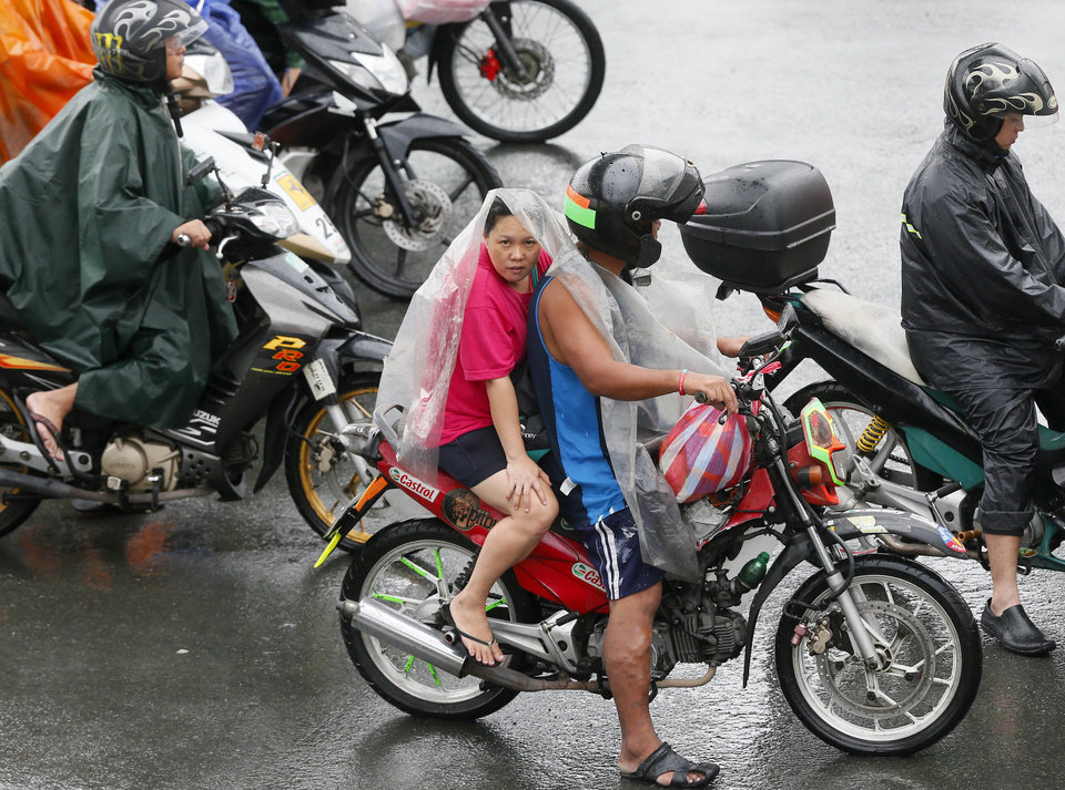 Photo - Motorists shield themselves during a slight rain brought about by typhoon Melor (local name