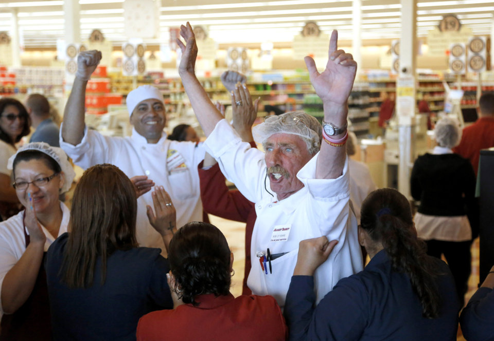 Photo - Market Basket meat manager Bob Dietz, of Methuen, Mass., center, raises his arms in celebration after watching a televised speech by restored Market Basket CEO Arthur T. Demoulas at a store location, Thursday, Aug. 28, 2014, in Chelsea. A six-week standoff between thousands of employees of the New England supermarket chain and management has ended with the news that beloved former CEO Demoulas is back in control after buying the entire company. Demoulas made his speech to workers in Tewksbury, Mass. (AP Photo/Steven Senne)