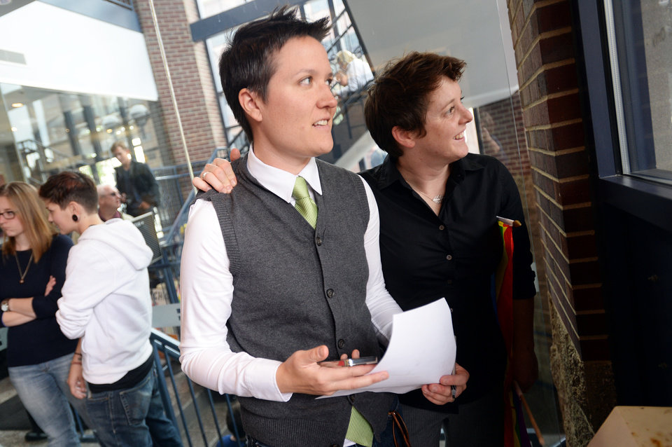 Photo - Lauren Rosenberg and her partner Chrissie George look out the window at Washtenaw County Clerk's Office as they wait for a potential decision that would overturn a ruling on Michigan's ban on same sex marriage on Wednesday, Oct. 16, 2013, in Ann Arbor, Mich. U.S. District Judge Bernard Friedman said he won't make a decision until after hearing testimony Feb. 25 from experts on whether there's a legitimate state interest in banning gay marriage. (AP Photo/The Ann Arbor News, Melanie Maxwell)