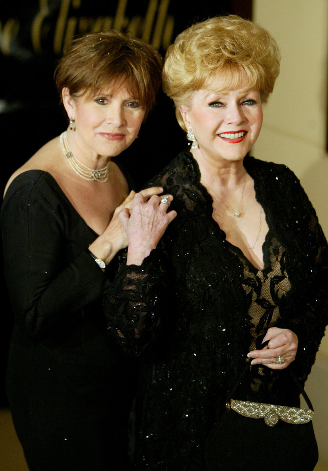 Photo - Carrie Fisher, left, and her mother Debbie Reynolds arrive at Elizabeth Taylors Diamond Jubilee birthday party at the Ritz Carlton Lake Las Vegas, Tuesday, Feb. 27, 2007. (AP Photo/Jane Kalinowsky) ORG XMIT: NVJK102