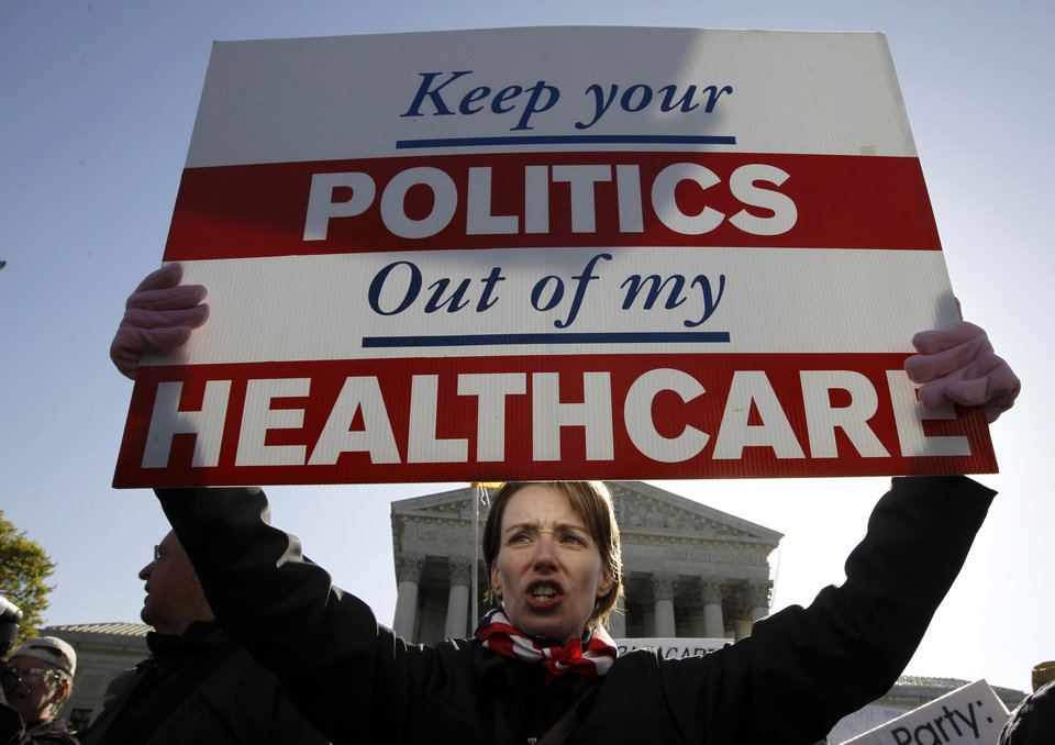 Photo -   Amy Brighton from Medina, Ohio, who opposes health care reform, rallies in front of the Supreme Court in Washington, Tuesday, March 27, 2012, as the court continues arguments on the health care law signed by President Barack Obama. (AP Photo/Charles Dharapak)