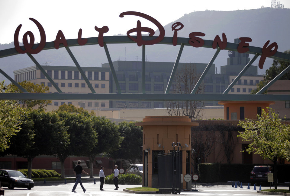 Photo - FILE - In this Feb. 8, 2011 file photo, people stand near the entrance to the Walt Disney Studios in Burbank , Calif. Disney said Monday March 24, 2014, that it is buying YouTube channel operator Maker Studios for $500 million as the family entertainment giant aims to stay in front of younger audiences who are increasingly watching short videos online. ( AP Photo/Jae C. Hong, File)