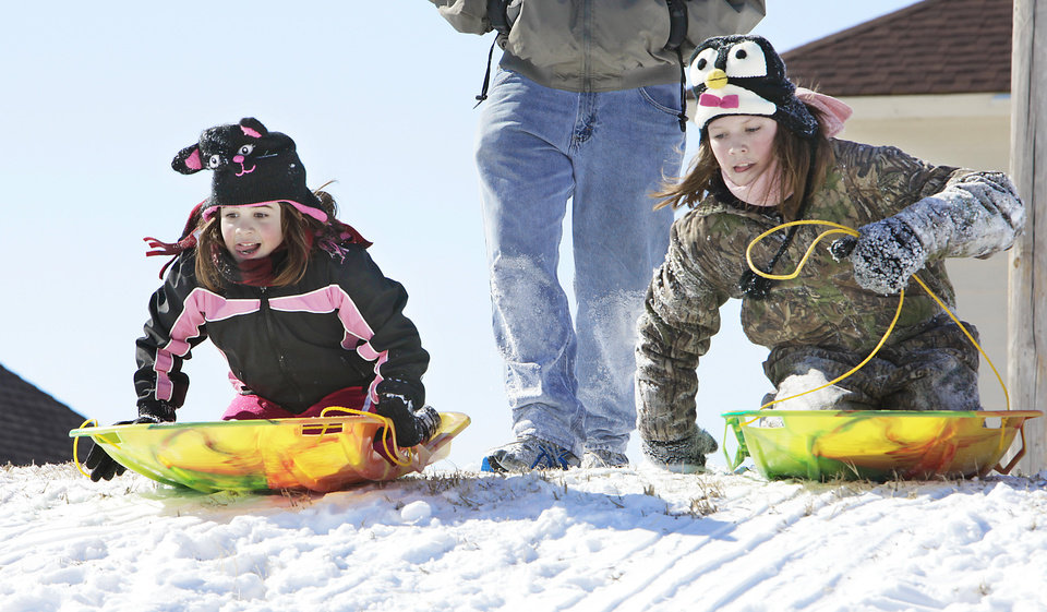 Photo - Katie Glathar, 7, and Zoe Hungate, 11, race on their snow sleds in a park in Fairfield addition in Edmond, Wednesday, February 2, 2011.        Photo by David McDaniel, The Oklahoman
