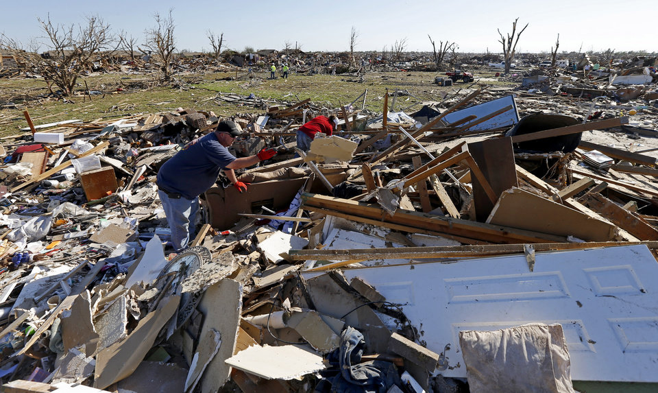 Chris and Jami Mundy sort through debris at their home in the Plaza Towers neighborhood in Moore, Okla., on Wednesday, May 22, 2013. The home was destroyed by a tornado that struck the area on Monday, May 20, 2013. Photo by Bryan Terry, The Oklahoman