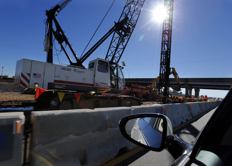 Photo - Construction crews contracted by the state Transportation Department work   in the center median of Interstate 35 near Main Street in Norman. PHOTO BY STEVE SISNEY, THE OKLAHOMAN  STEVE SISNEY