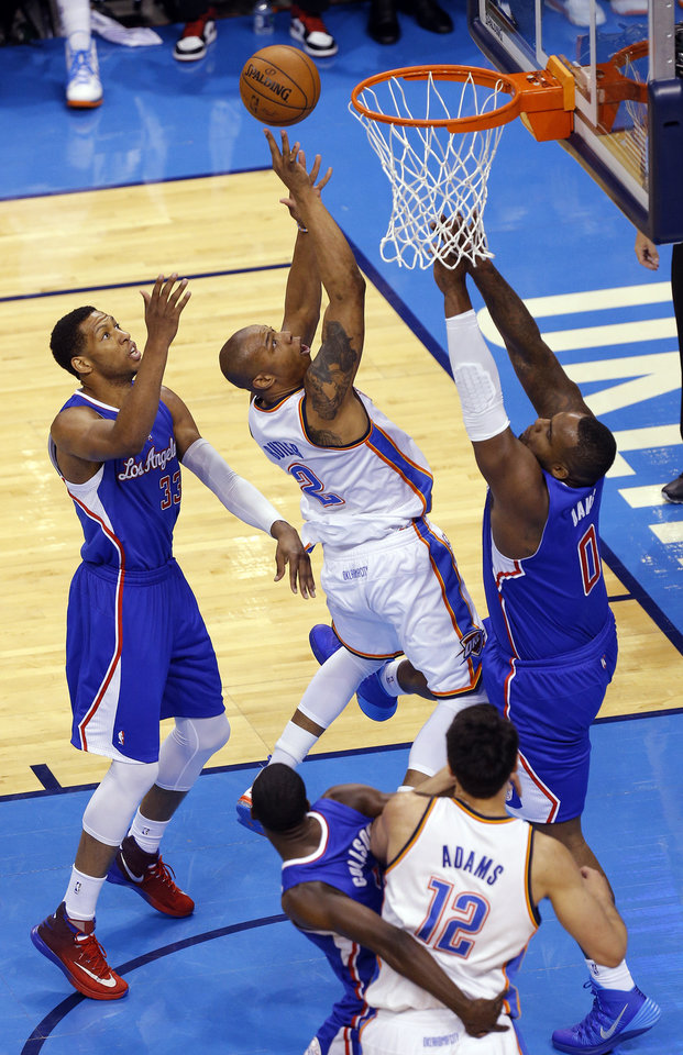 Photo - Oklahoma City's Caron Butler (2) shoots between Los Angeles' Danny Granger (33) and Glen Davis (0) during Game 1 of the Western Conference semifinals in the NBA playoffs between the Oklahoma City Thunder and the Los Angeles Clippers at Chesapeake Energy Arena in Oklahoma City, Monday, May 5, 2014. Photo by Bryan Terry, The Oklahoman