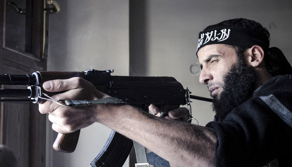 Photo -   In this Sunday, Nov. 4, 2012 photo, a sniper of the Ahmad Assaf Syrian rebel platoon takes aim at Syrian army positions in Aleppo, Syria. (AP Photo/Mustafa Karali)