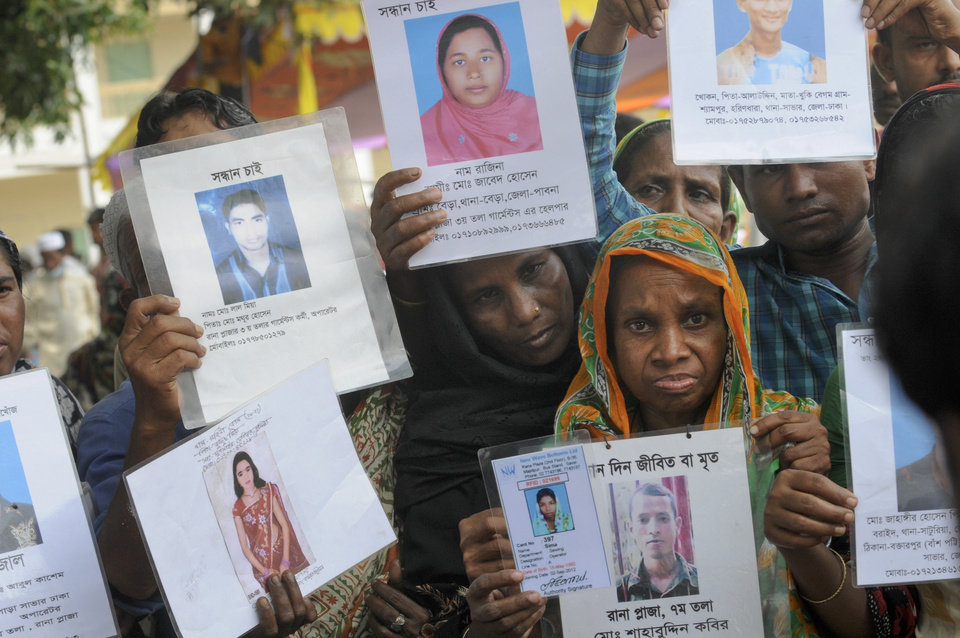 Photo - Bangladeshis display portraits of missing relatives at a makeshift morgue in Savar near Dhaka, Bangladesh, Wednesday May 8, 2013. Dozens of bodies recovered Wednesday from the building were so decomposed they were being sent to a lab for DNA identification, police said, as the death toll from Bangladesh's worst industrial disaster topped 800. (AP Photo/Ismail Ferdous)