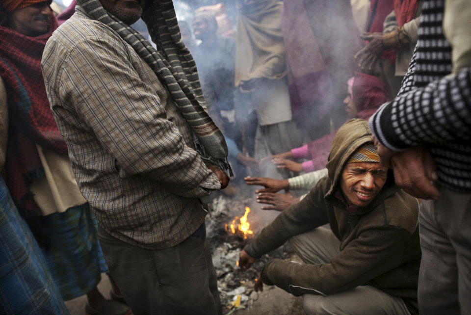 Indian laborers warm themselves on a fire in a market on a cold morning in New Delhi, India, Monday, Jan. 7, 2013. North India continues to face below average weather conditions with dense fog affecting flights and trains. More than 100 people have died of exposure as northern India deals with historically cold temperatures. (AP Photo/Kevin Frayer)