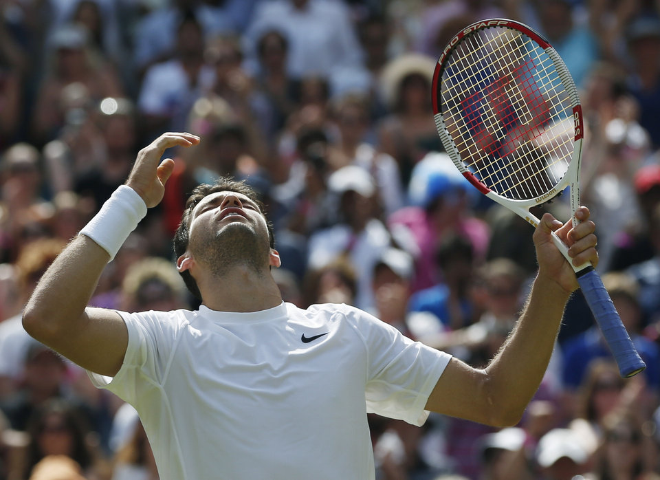 Photo - Grigor Dimitrov of Bulgaria celebrates after defeating defending champion Andy Murray of Britain in their men's singles quarterfinal match at the All England Lawn Tennis Championships in Wimbledon, London, Wednesday July 2, 2014. (AP Photo/Pavel Golovkin)