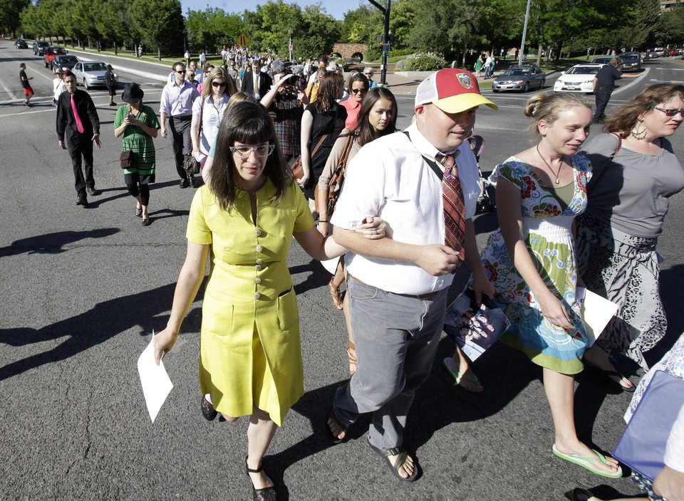 Photo - Kate Kelly, left, walks with supporters to the Church Office Building of the Church of Jesus Christ of Latter-day Saints Sunday, June 22, 2014, in Salt Lake City. While  Kelly's former church leaders meet in Virginia on Sunday night to decide if she'll be ousted from her church, the founder of a prominent Mormon women's group will hold a vigil in Salt Lake City along with hundreds of her supporters.   (AP Photo/Rick Bowmer)