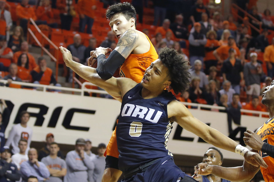 Photo - Oklahoma State's Lindy Waters III (21) grabs a rebound beside Kevin Obanor (0) of Oral Roberts during an NCAA basketball game between the Oklahoma State University Cowboys (OSU) and the Oral Roberts Golden Eagles (ORU) at Gallagher-Iba Arena in Stillwater, Okla., Wednesday, Nov. 6, 2019. Oklahoma State won 80-75. [Bryan Terry/The Oklahoman]
