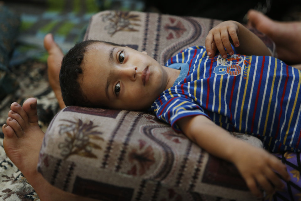 Photo - Two and a half-year-old Muhammad Al Masri rests on his mother's legs in a classroom at a United Nations school where hundreds of families have sought refuge after fleeing their homes following heavy Israeli forces' strikes, in Jebaliya refugee camp, Gaza Strip, Friday, July 25, 2014. Over 140,000 Palestinians are seeking shelter in 83 UNRWA schools, according to UNRWA spokesman Chris Gunness. The number of Palestinians seeking shelter since the ground operation began has increased seven-fold. (AP Photo/Lefteris Pitarakis)