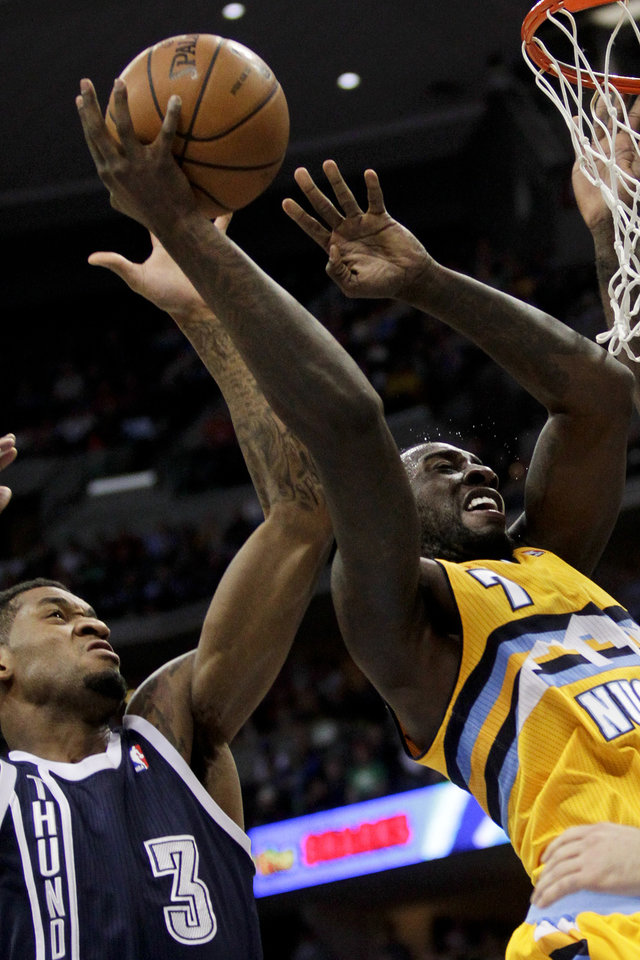 Photo - Oklahoma City Thunder's Perry Jones (3) tries to block a shot by Denver Nuggets power forward J.J. Hickson (7) during the first quarter of an NBA basketball game Thursday, Jan. 9, 2014, in Denver. (AP Photo/Barry Gutierrez)