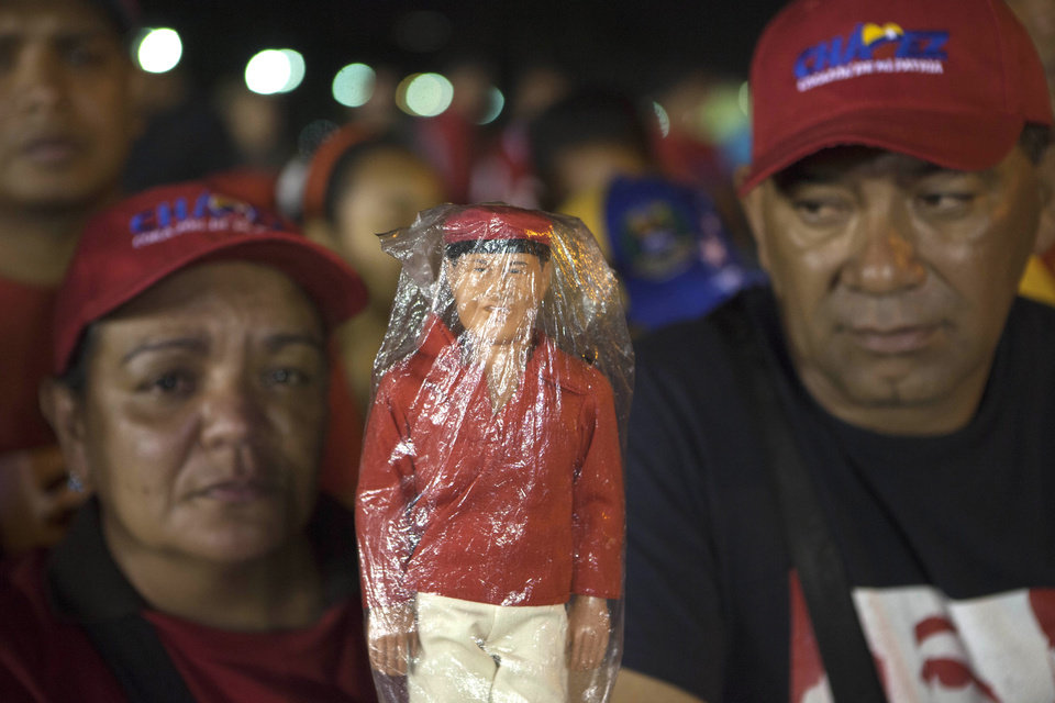 Supporters hold a doll depicting of the late President Hugo Chavez as they wait in line to see his body outside the Fort Tiuna military academy in Caracas, Venezuela, Wednesday, March 6, 2013. Chavez\'s body will lie in sate at the academy until his funeral, scheduled for Friday. (AP Photo/Esteban Felix)