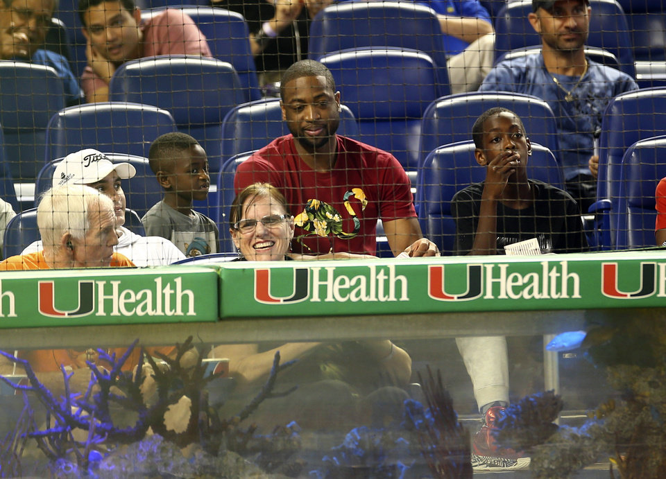 Photo - Miami Heat basketball player Dwyane Wade, center, watches a baseball game between the Chicago Cubs and Miami Marlins in Miami, Wednesday, June 18, 2014.  (AP Photo/J Pat Carter)