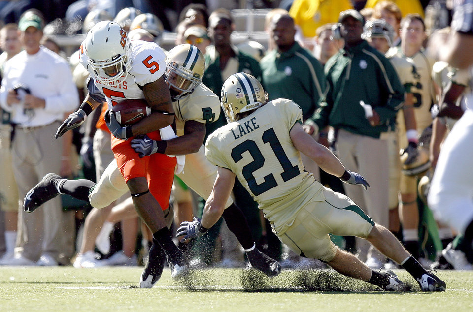 Photo - OSU's Keith Toston (5) is tackled by Baylor's Jeremy Williams (4) and Jordan Lake (21) during the college football game between Baylor University and Oklahoma State University (OSU) at Floyd Casey Stadium in Waco, Texas, Saturday, Oct. 24, 2009.  Photo by Sarah Phipps, The Oklahoman
