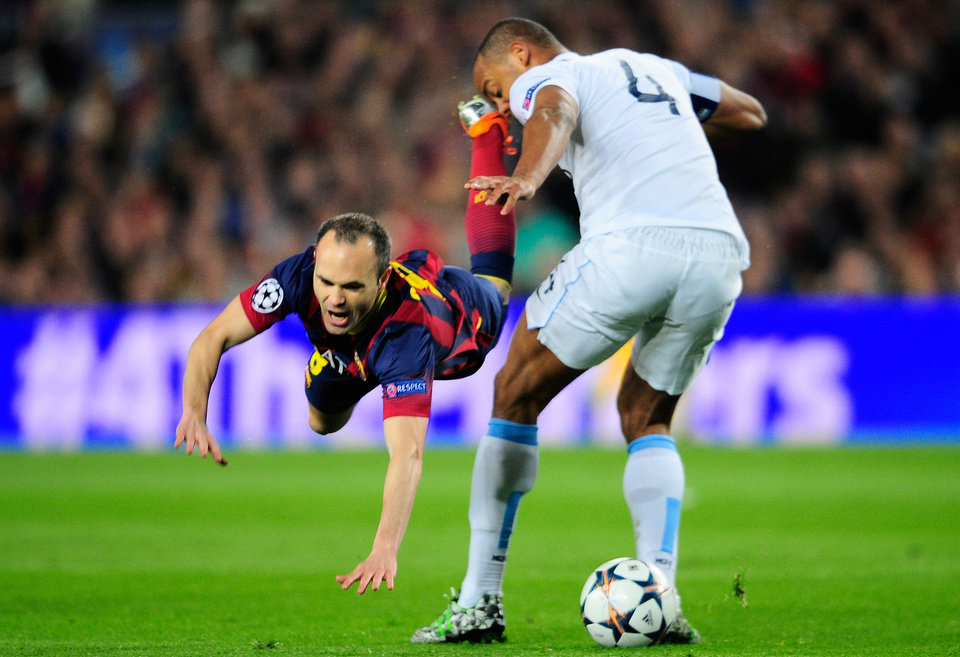 Photo - Barcelona's Andres Iniesta, left, falls in front of Manchester City's Vincent Kompany during a Champions League, round of 16, second leg, soccer match between FC Barcelona and Manchester City at the Camp Nou Stadium in Barcelona, Spain, Wednesday March 12, 2014. (AP Photo/Manu Fernandez)