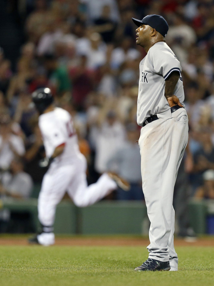 Photo - CORRECTS PERSON WHO HIT HOME RUN TO MIKE NAPOLI, INSTEAD OF JONNY GOMES - New York Yankees' CC Sabathia watis as Boston Red Sox's Mike Napoli, left, rounds third base on a three-run home run in the third inning of a baseball game in Boston, Sunday, July 21, 2013. (AP Photo/Michael Dwyer)
