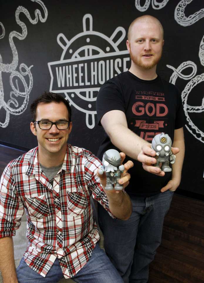 Wheelhouse Co. creators James Hugo, left, and Chase Layman show a couple of vinyl toys from their Rivals line Monday at their office in Edmond.  Photo By Paul Hellstern, The Oklahoman