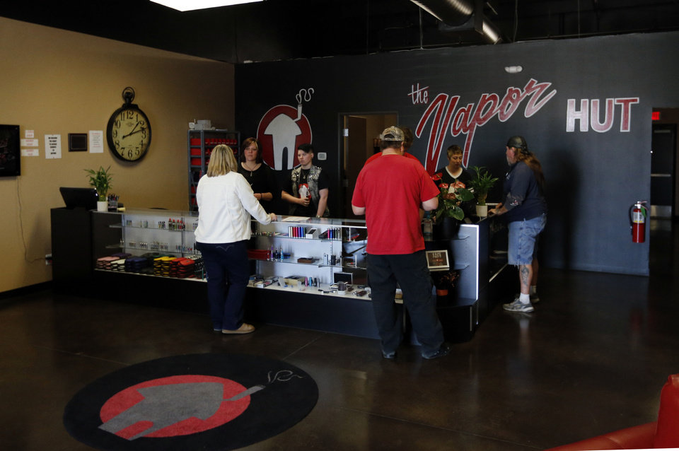 Photo - Customers shop for e-cigarette supplies at the Oklahoma City-based ecigarette chain The Vaport Hut on Friday, Jan. 17, 2014.  STEVE SISNEY - The Oklahoman