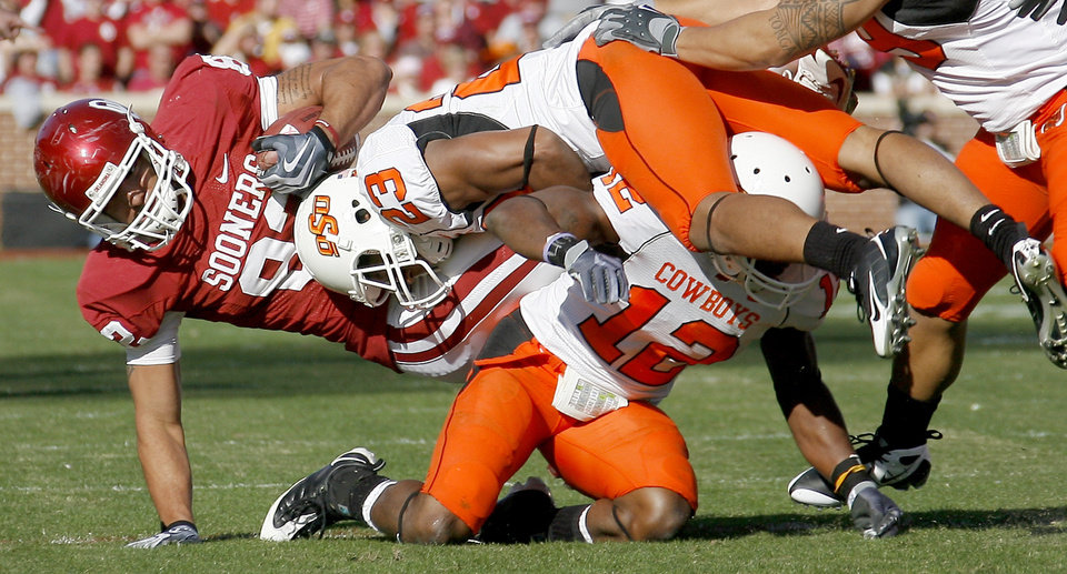 Photo - OU's James Hanna is brought down by OSU's Terrance Anderson, center, and Johnny Thomas during the second half of the Bedlam college football game between the University of Oklahoma Sooners (OU) and the Oklahoma State University Cowboys (OSU) at the Gaylord Family-Oklahoma Memorial Stadium on Saturday, Nov. 28, 2009, in Norman, Okla.Photo by Bryan Terry, The Oklahoman