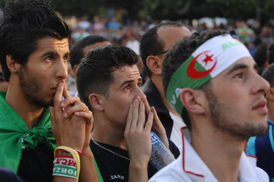Photo - In this photo dated Tuesday, June 17, 2014, an Algerian soccer fans react while watching his team's World Cup soccer match with Belgium on a large screen set up in Algiers Zocalo June 17, 2014. Belgium defeated Algeria 2-1. (AP Photo/Sidali Djarboub)