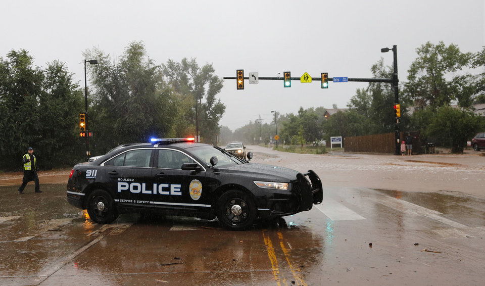 Photo - A police officer blocks a closed road following overnight flash flooding, Boulder, Colo., Thursday, Sept 12, 2013. The widespread high waters are keeping search and rescue teams from reaching stranded residents and motorists in Boulder and nearby mountain communities as heavy rains hammered northern Colorado. (AP Photo/Brennan Linsley)
