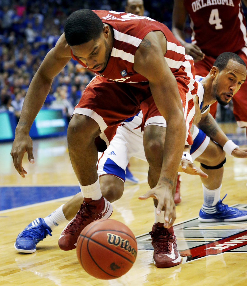 Photo - Oklahoma forward Cameron Clark (21) reaches for the ball while covered by Kansas guard Travis Releford (24) during the second half of an NCAA college basketball game in Lawrence, Kan., Saturday, Jan. 26, 2013. Kansas won 67-54. (AP Photo/Orlin Wagner) ORG XMIT: KSOW109