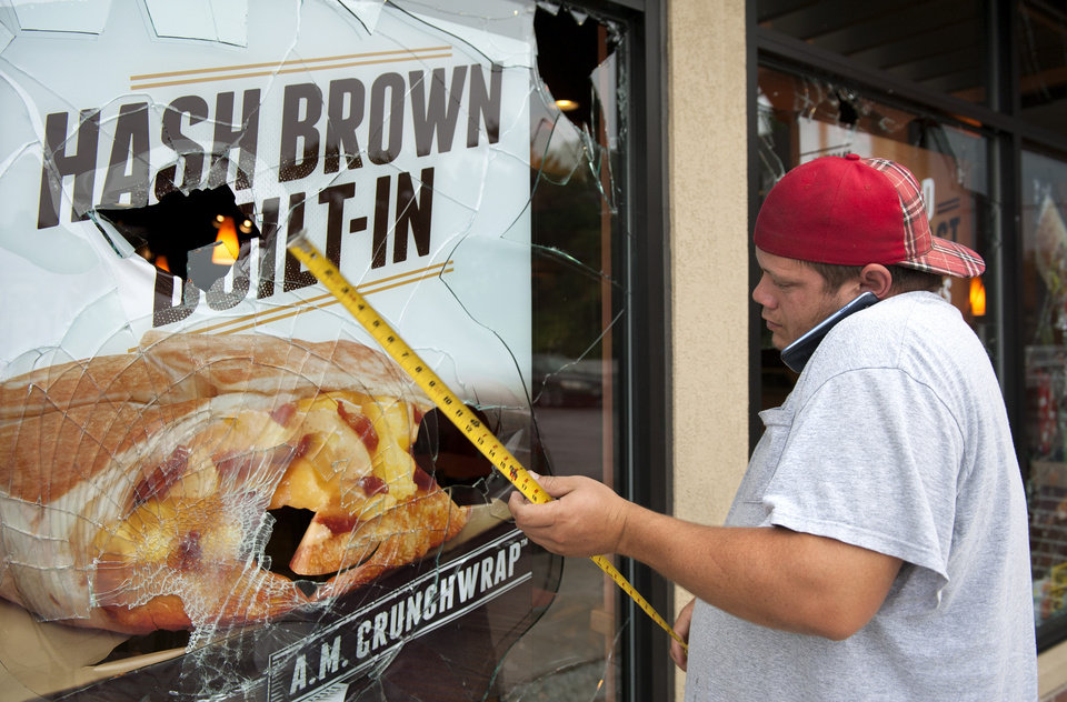 Photo - Kevin Nelke, of A-Affordable Glass, takes measurements and calls in an order Monday, Aug. 11, 2014, while repairing the windows of a Taco Bell looted during the violence that erupted in Ferguson, Mo. overnight following a candle-light memorial for 18-year-old shooting victim Michael Brown. Police said Brown, who was unarmed, was fatally shot Saturday in a scuffle with an officer.  (AP Photo/Sid Hastings)