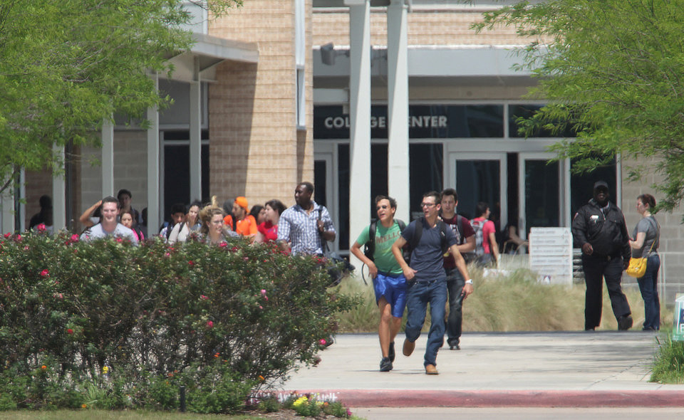 Photo - Students run from the Lone Star College's Cypress-Fairbanks campus Tuesday, April 9, 2013, in Cypress, Texas.At least 14 people were hurt in a stabbing at the campus Tuesday.  (AP Photo/Houston Chronicle, James Nielsen)