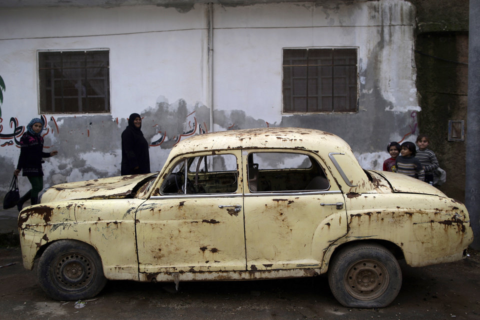 Syrian women walk by an old abandoned car parked on a roadside in Maaret Misreen, near Idlib, Syria, Thursday, Dec. 13, 2012. (AP Photo/Muhammed Muheisen) ORG XMIT: XMM105