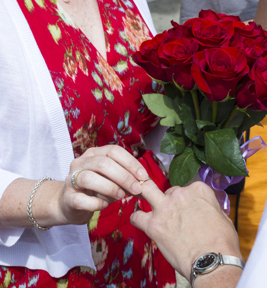 Photo - Sara Hinkel places a ring on Kerry Lehman, during their wedding ceremony Saturday, June 7, 2014, in Madison, Wis. The partners, both of Madison, have been together for 14 years. On Friday a federal judge struck down the state's gay marriage ban. (AP Photo/Andy Manis)