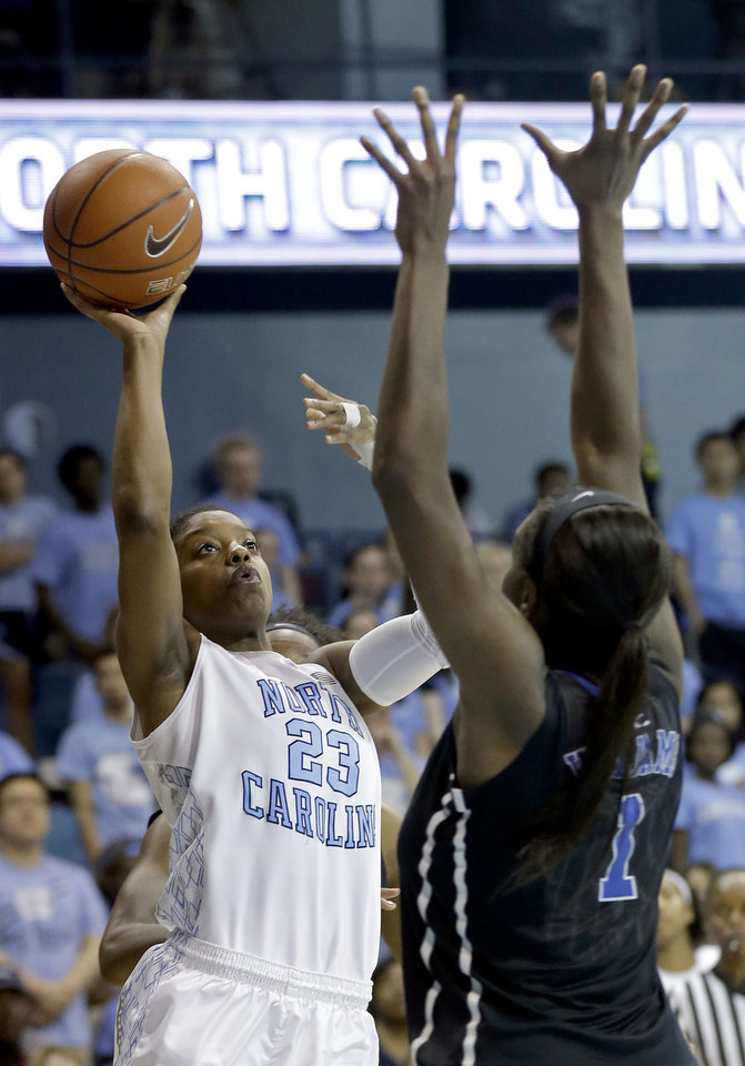 Photo - Duke's Elizabeth Williams (1) defends as North Carolina's Diamond DeShields (23) shoots during the second half of an NCAA college basketball game in Chapel Hill, N.C., Sunday, March 2, 2014. North Carolina won 64-60. (AP Photo/Gerry Broome)