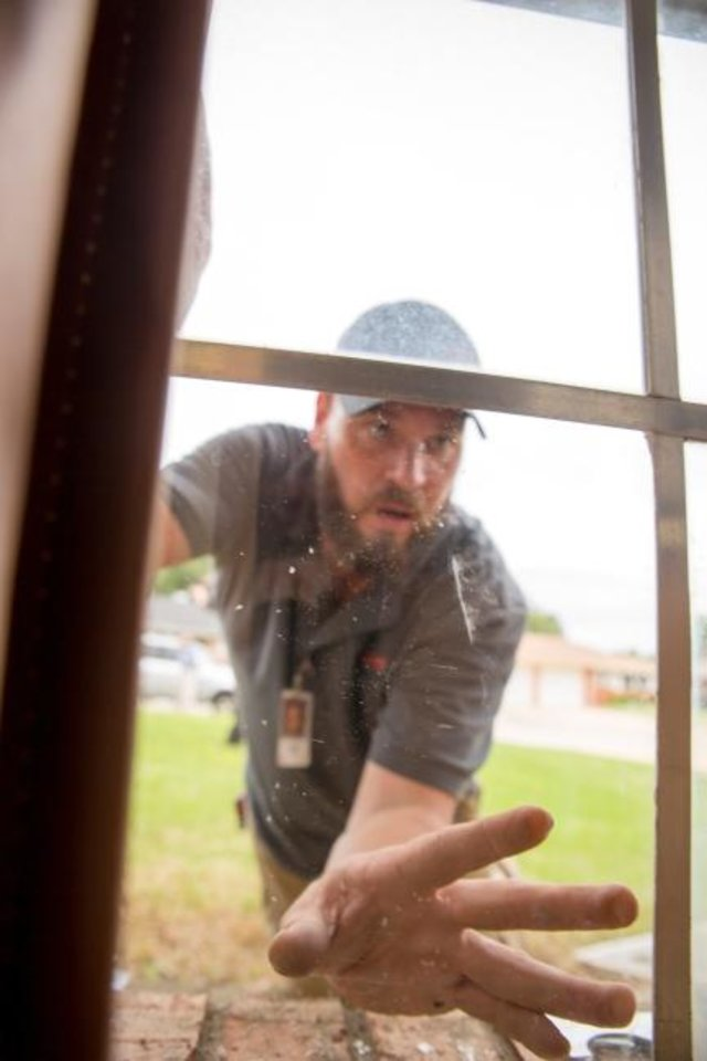 Photo -  A contractor evaluates a window during OG&E's Silver Energy Sweep initiative in south Oklahoma City.