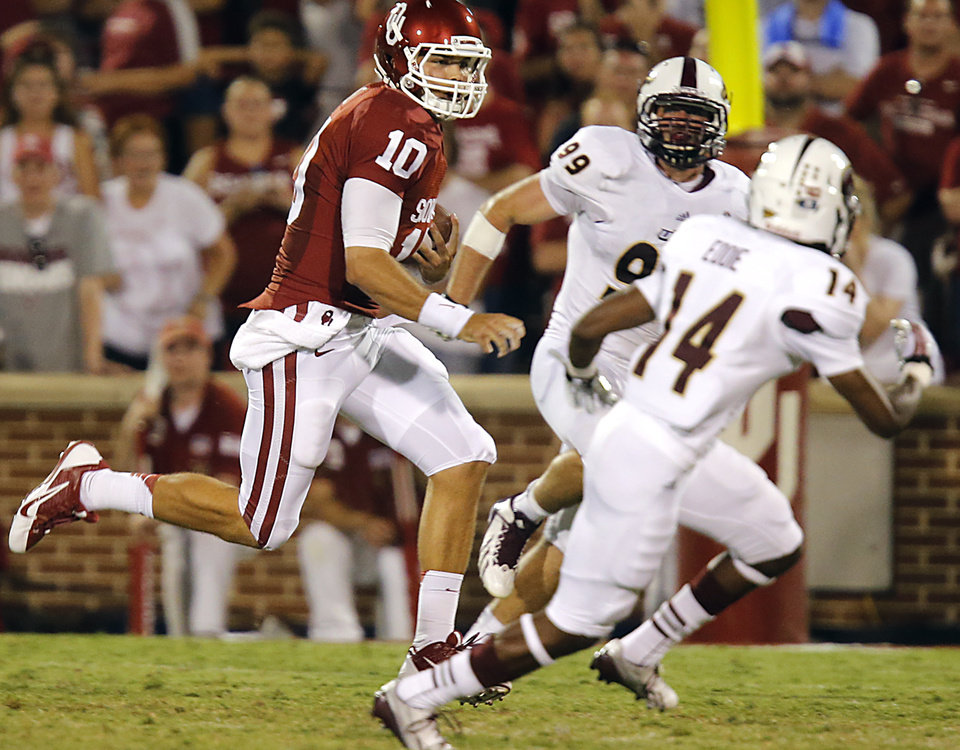 Oklahoma's Blake Bell (10) runs past Louisiana Monroe's Vincent Eddie (14) and Joey Gautney (99) during the college football game between the University of Oklahoma Sooners (OU) and the University of Louisiana Monroe Warhawks (ULM) at the Gaylord Family Memorial Stadium on Saturday, Aug. 31, 2013 in Norman, Okla.  Photo by Chris Landsberger, The Oklahoman