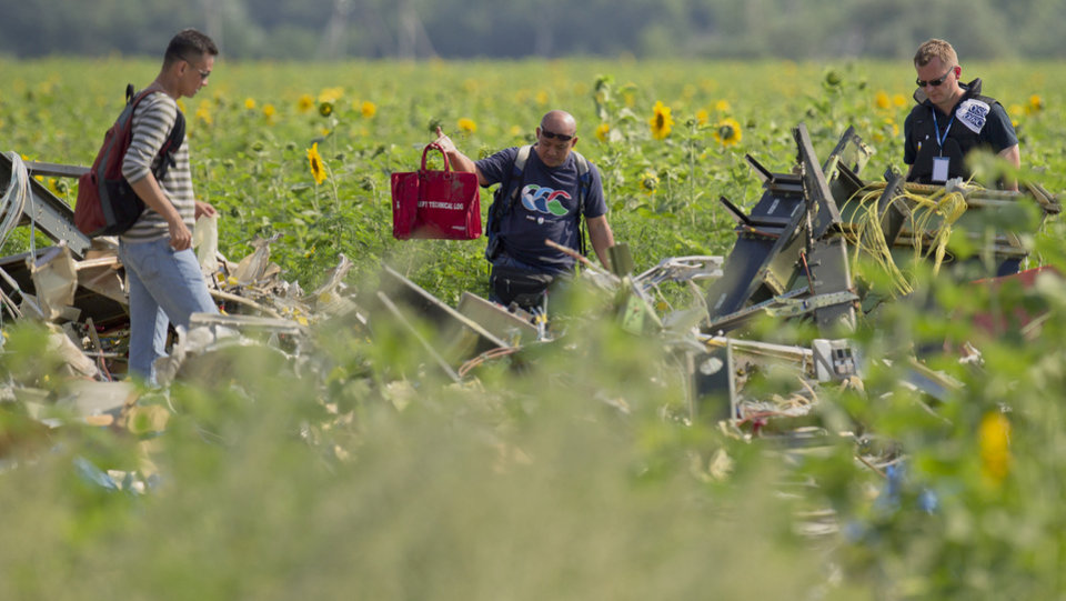Photo - A Malaysian air crash investigator holds a bag at a crash site of Malaysia Airlines Flight 17 in the village of Rozsypne, eastern Ukraine, Tuesday, July 22, 2014. A team of Malaysian investigators visited the site along with members of the OSCE mission in Ukraine for the first time since the air crash last week.(AP Photo/Vadim Ghirda)