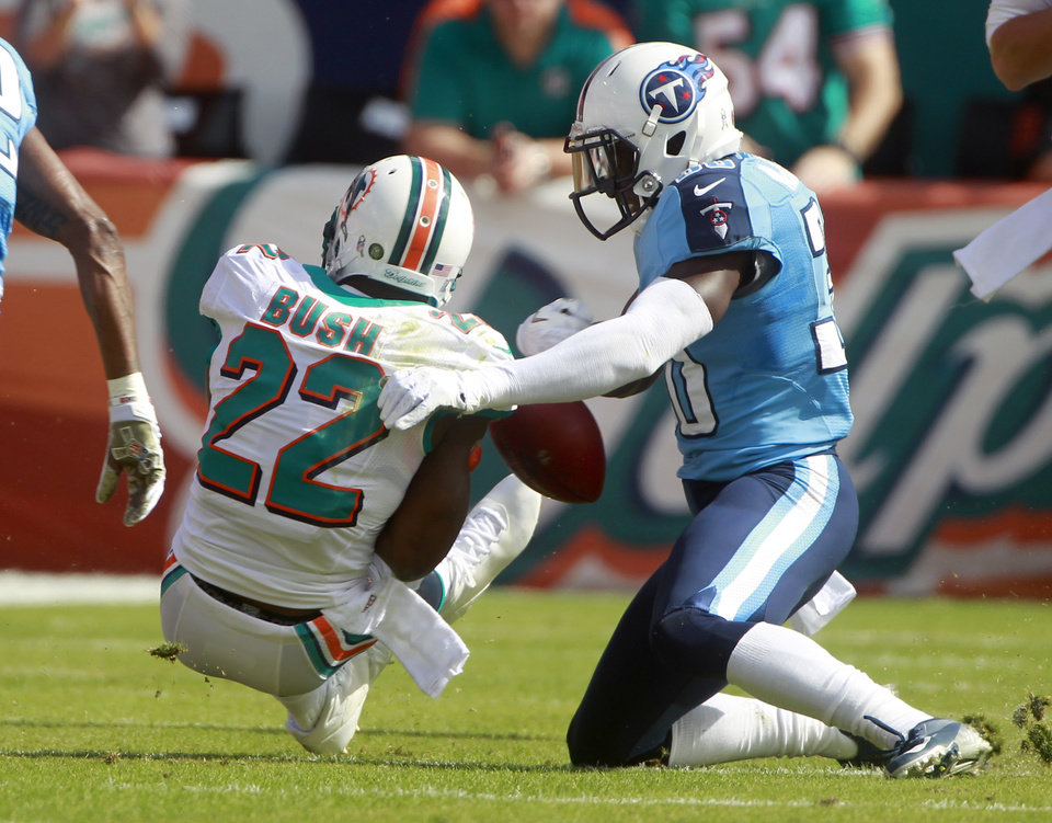 Photo -   Miami Dolphins running back Reggie Bush (22) fumbles the ball as he is tackled by Tennessee Titans cornerback Jason McCourty, right, during the first half of an NFL football game, Sunday, Nov. 11, 2012, in Miami, Fla. (AP Photo/John Bazemore)