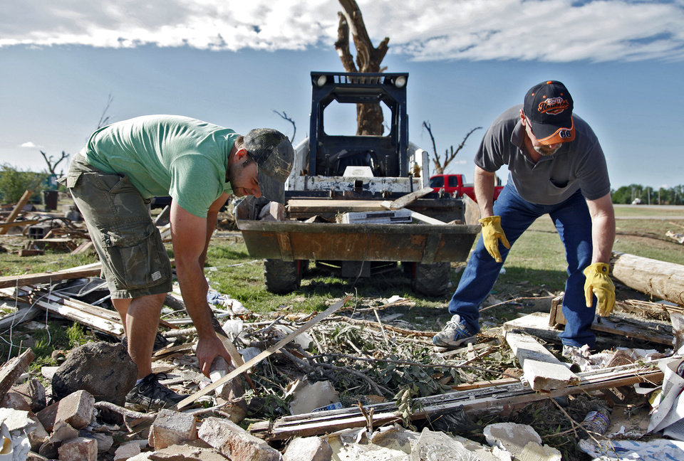 Photo - J.T. Chronister, left, and Joe Jainese dig through rubble from a home destroyed by Tuesday's tornado north of El Reno, Wednesday, May 25, 2011. Photo by Chris Landsberger, The Oklahoman