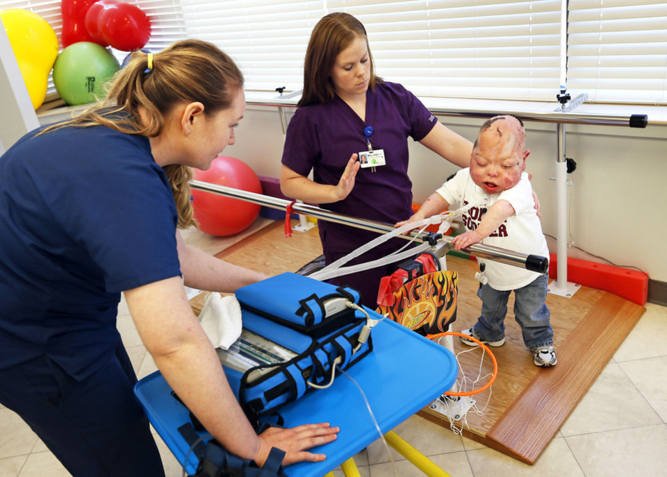 Photo - Jennifer Batts, a physical therapy student, left, and Melanie Connel, a physical therapist, work with Fletcher Burns, 8, at The Children's Center in Bethany. Photos by Nate Billings, The Oklahoman