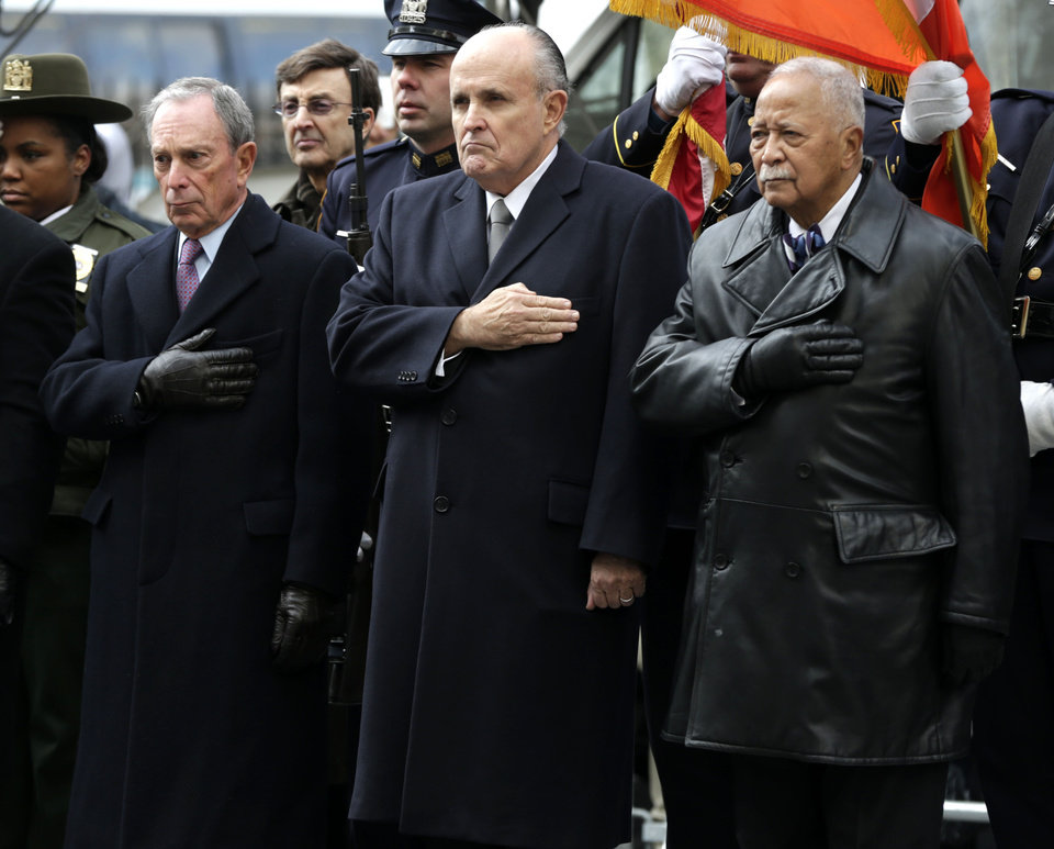 Photo - New York City Mayor Michael Bloomberg, left, and former New York City Mayors Rudolph Giuliani, center, and David Dinkins put their hands over their hearts as a casket containing the body of former New York City Mayor Ed Koch leaves a synagogue after his funeral in New York, Monday, Feb. 4, 2013. Koch was remembered as the quintessential New Yorker during a funeral that frequently elicited laughter, recalling his famous one-liners and amusing antics in the public eye. (AP Photo/Seth Wenig)