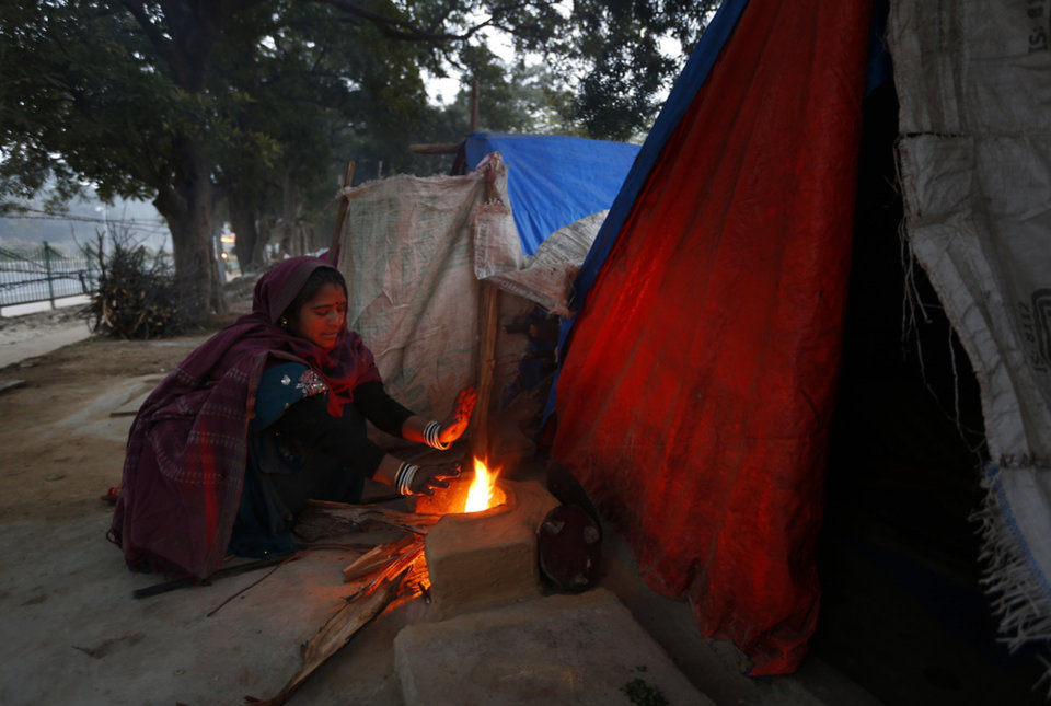 A woman warms herself by a fire to to stay warm in New Delhi, India, Tuesday, Jan. 8, 2013. North India continues to face below average weather conditions with dense fog affecting flights and trains. More than 100 people have died of exposure as northern India deals with historically cold temperatures. (AP Photo/ Saurabh Das)