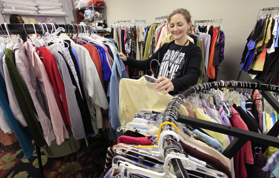 Photo -  BELOW: Debbie Ashford of Edmond, director of No Boundaries International's Carina's Closet, sorts through donated clothing at the clothing distribution site. Photo by Paul B. Southerland, The Oklahoman       PAUL B. SOUTHERLAND - PAUL B. SOUTHERLAND
